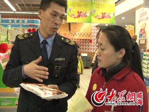 执法人员跟超市工作人员介绍汤圆的储存条件